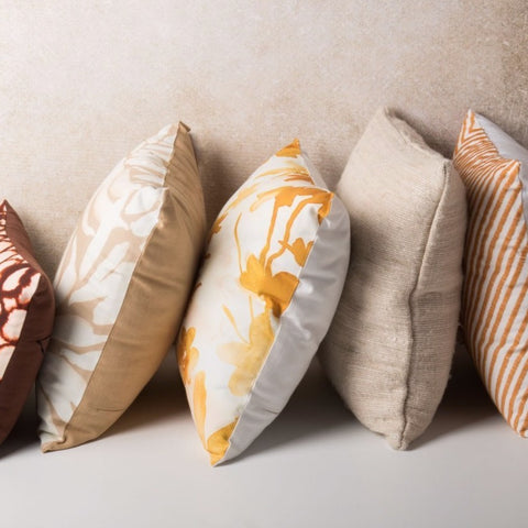 Five cushions in a row. Small red design cushion. Square white and tan cushion. Square yellow print cushion. Square sand cushion. Square Arrabida cushion in Buckskin.