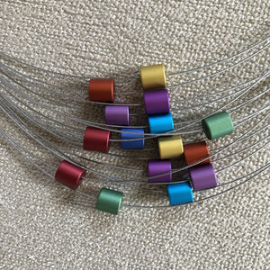 Rainbow assortment of multi colored metal cylinders on a MOOI necklace.