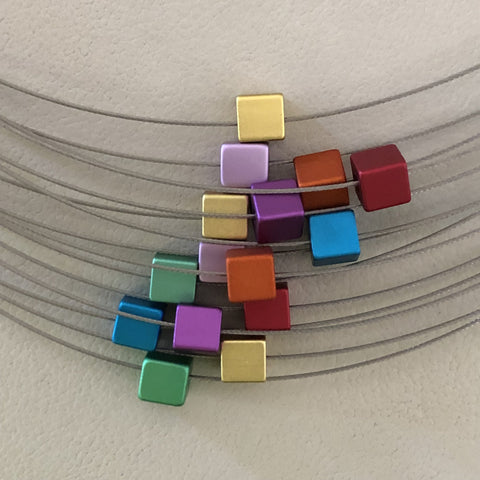 Beautiful metal multi colored necklace by MOOI. Metallic cubes in red, orange, green, blue, purple, and gold.