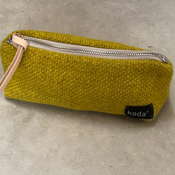 Full body view of the yellow small triangle accessory pouch by KODA.
