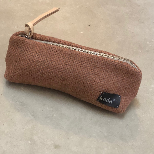 Full body view of the salmon + grey small accessory triangle pouch by KODA.