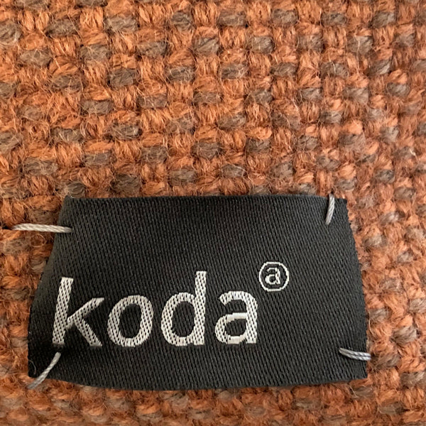 Closeup of the salmon + grey small triangle accessory pouch with KODA tag.