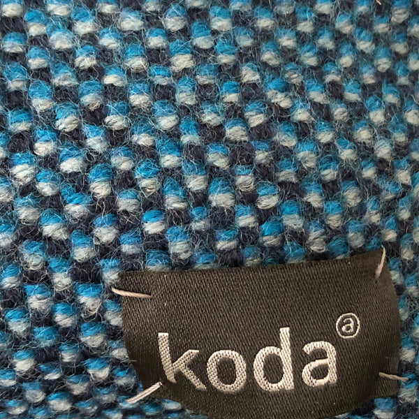Closeup of the blue + black + grey checkered small triangle accessory pouch with KODA tag.