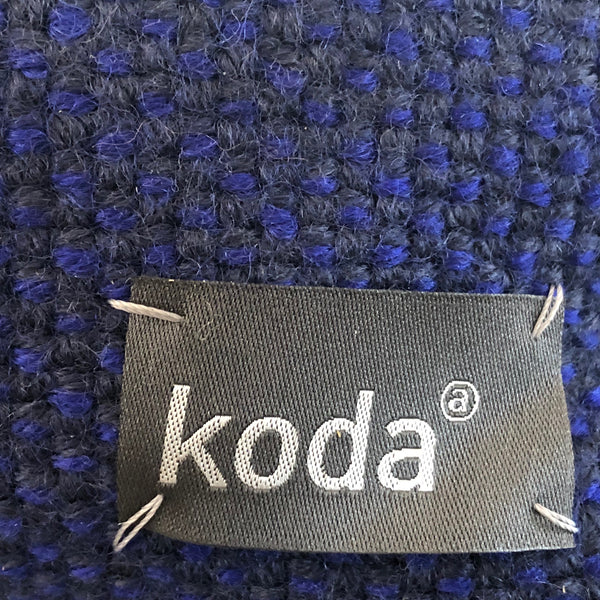 Closeup of the navy triangle accessory pouch with KODA tag.
