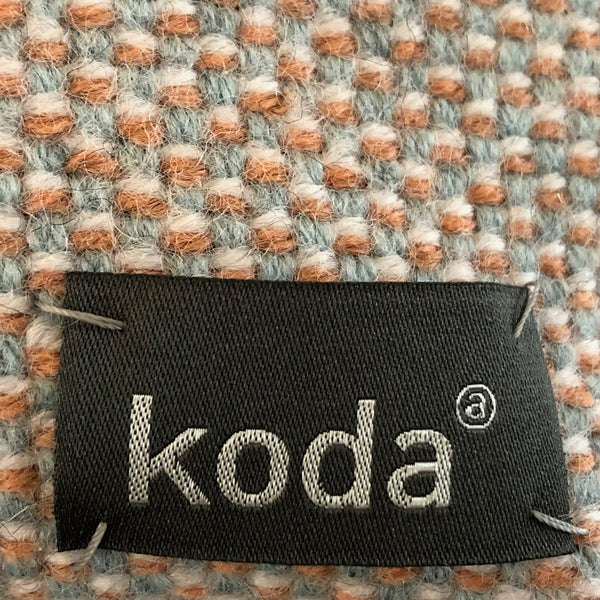 Closeup of the yellow + white + grey + salmon checkered small triangle accessory pouch with KODA tag.