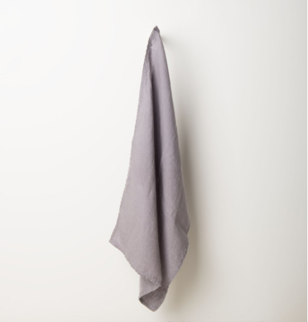 A gray Linen Tea Towel by Urban Nature Culture hanging against a white wall.