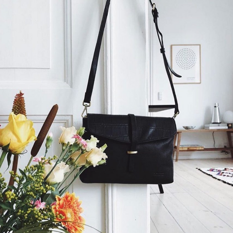 The black Ella Midi Bag by O My Bag hanging against a white wall