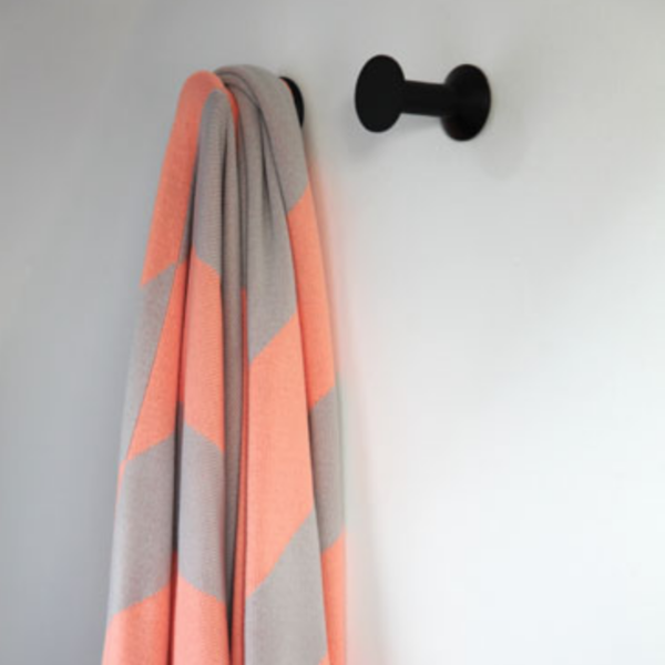 Two Haak Wall Hooks by ONSHUS in black hanging on a white wall. One hook is holding a gray and orange towel.