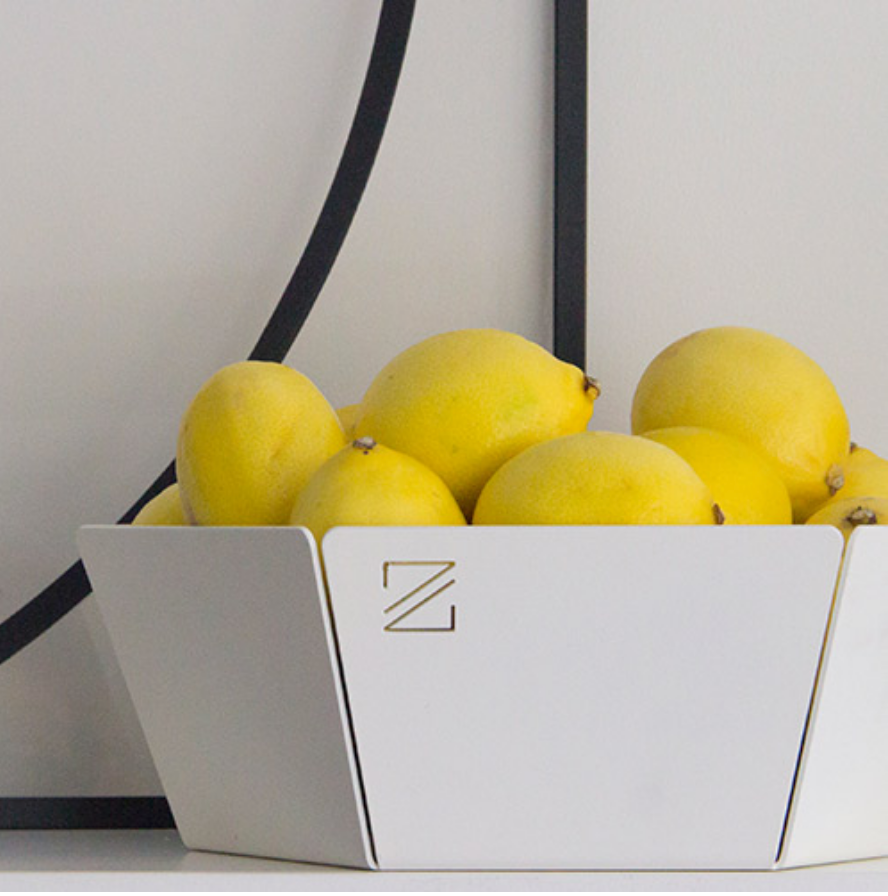 The white fruit bowl jut by ZOOI filled with lemons. A modern home kitchen bowl.