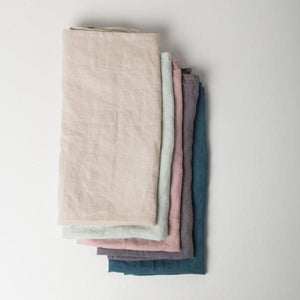Stack of five linen tea towels by Urban Nature Culture. Sand color on top followed by celadon, old pink, gray, and petrol.