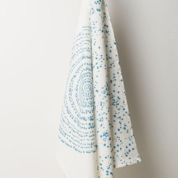 Kuba Art tea towel by Urban Nature Culture hanging against a white wall. White towel with blue dot design.