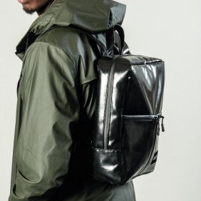 The Alberty Cuyp waterproof backpack in black modeled in black.