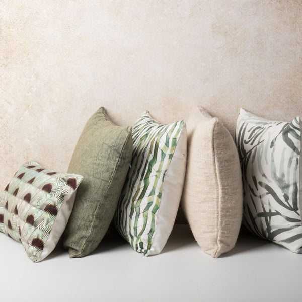 Five cushions by Urban Nature Culture against a beige background.