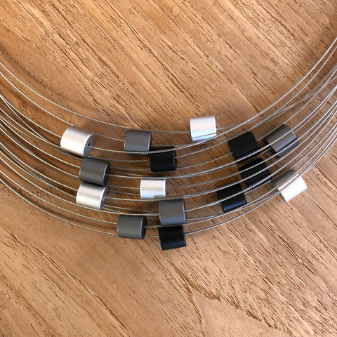 A unique piece of modern jewelry by MOOI. A 15-strand necklace with black, grey + silver cylinders.
