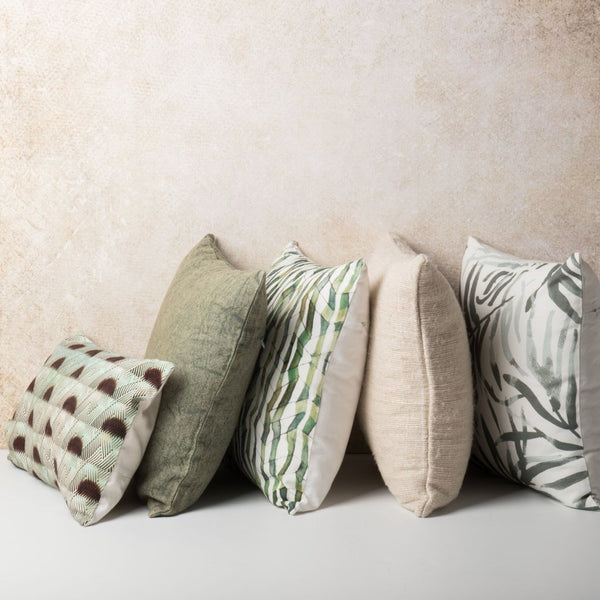 Five cushions from Urban Nature Culture. A small patterned cushion, green square cushion, green patterned cushion, light pink cushion, and the Flor Verde cushion.