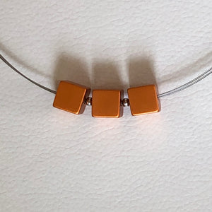 Three lightweight metal orange cubes on silver necklace by MOOI