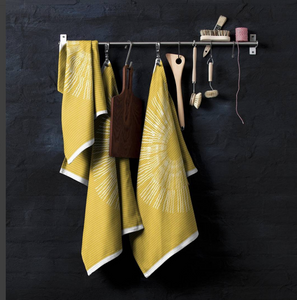 Three Osaka Tea Towels in yellow hanging against a black wall.