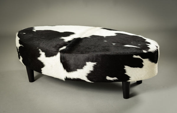 Black and white cowhide oval ottoman by Gorgeous Creatures
