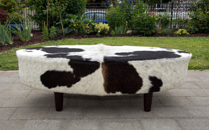 Brown and white oval cowhide ottoman by Gorgeous Creatures