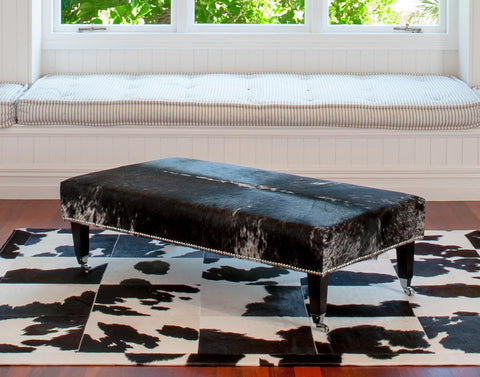 Image of Cowhide Ottoman with Wood Legs 130x70x38cm Studs & Caster wheels