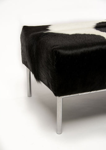 Image of Black & white cowhide ottoman with metal feature rail base 110cm x 50cm x 40cm tall.
