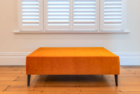 Bright orange velvet ottoman