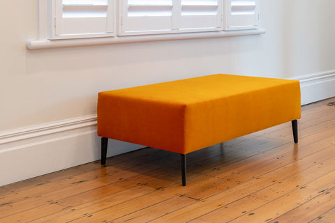 Image of Bright orange velvet ottoman