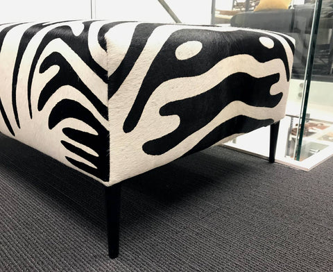 Image of Zebra cowhide ottoman furniture with black metal legs