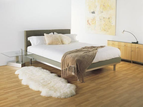 Image of Ivory Wool Sheepskin Rug next to Queen bed