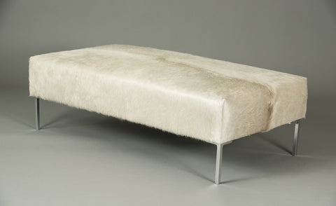 Natural off-white cow skin ottoman. A large rectangle with Stiletto metal legs.