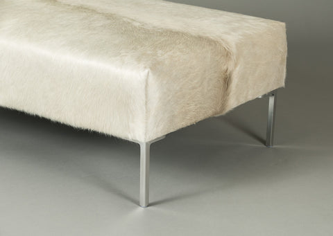 Image of Natural off-white cow skin ottoman. A large rectangle with Stiletto metal legs.
