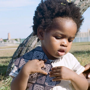 Small child holding indigo Creole flashcard in park