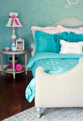Photo of a bedroom. The wall is painted in a textured faux finish. White bed frame with turquoise bedding. A small silver side table with lamp is on the left.