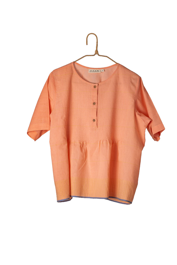 Pastel peach cotton top made from pure cotton material. Affordable sustainable clothes made in India. The top has short sleeves, button-down placket, and a round neck. It has contrast selvedge details at the hem. This top is perfect for summer holidays, casual meets, day to day wear.
