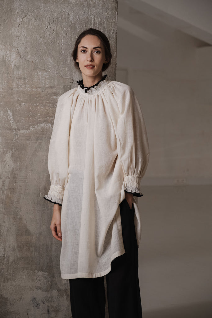 Off white vintage style organic cotton tunic with smocking at the neck and sleeves. It has a closed neck with gathers and full sleeves.Ethical clothing brands list. Organic clothing for bulk buy in USA, UK, Japan. Boutiques in India. all cotton clothing brands. Vintage style clothing.