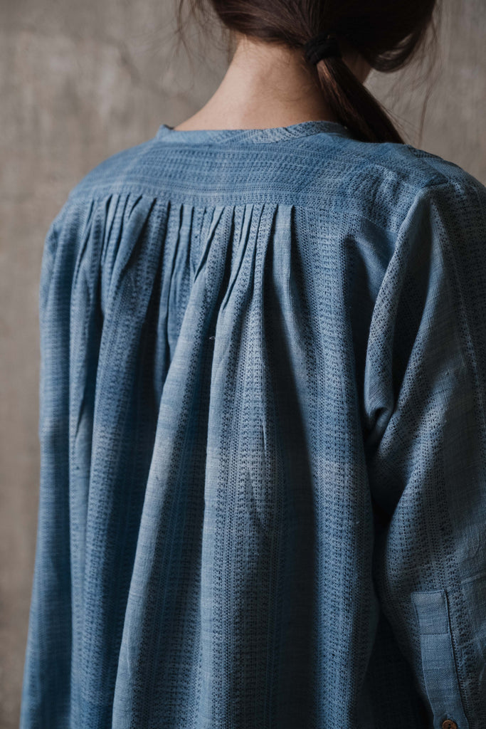 Earth friendly clothing. Indigo dyed tunic with closed neck with delicate gathers at the front and back, a button-down placket, and cuffed sleeves. It is paired with barrel fit black pants made from organic cotton fabric.