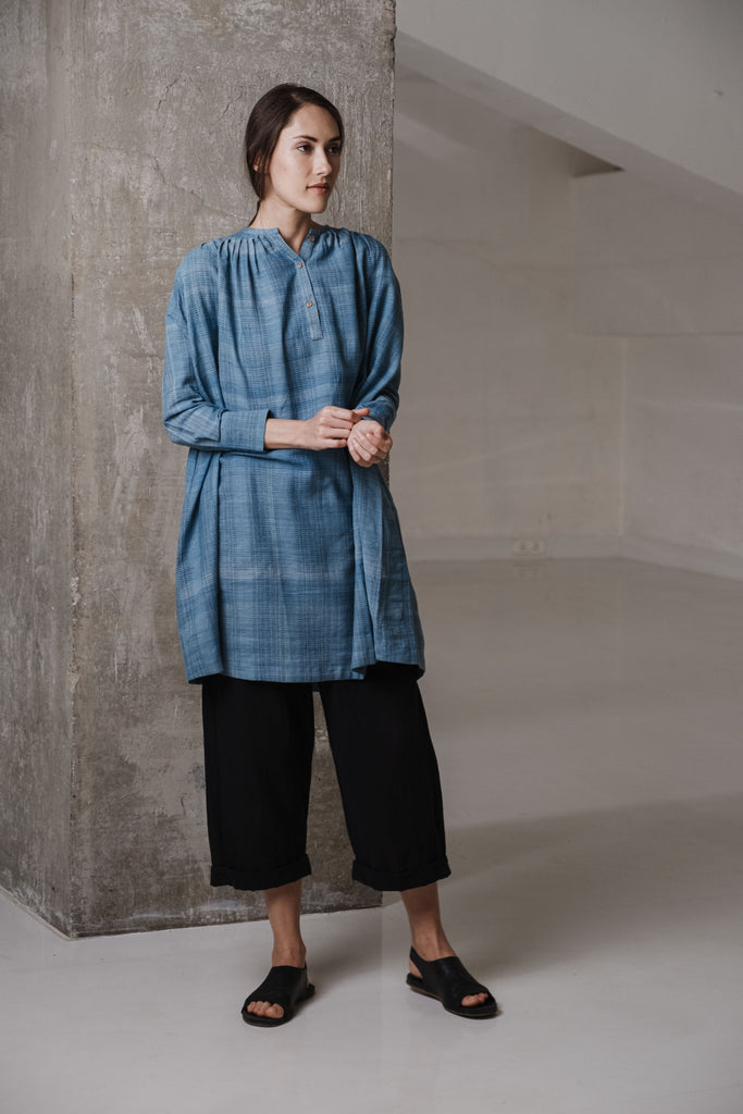 Classic summer clothes. Contemporary women's clothing brands. Indigo tunic with closed neck and delicate gathers at the front and back, a button-down placket, and cuffed sleeves. Black pants with barrel fit, drawstring waist, and roll-up hem. Modernized co-ord sets.