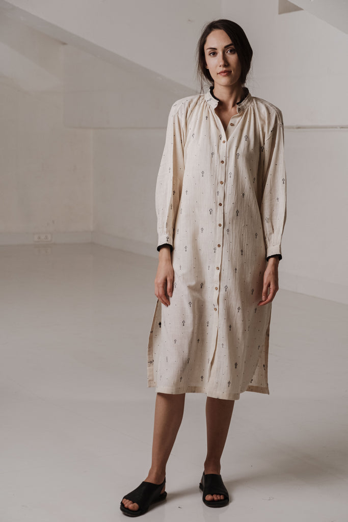 Essential Off white shirt dress detailed with black handwoven motifs. It has soft gathers around the neck, button down placket and side slits. Eco friendly clothing. cotton clothes online. Women wear clothing made from 100% cotton fabric.This tunic can be worn for everyday wear, casual meets, formal gatherings and travel.
