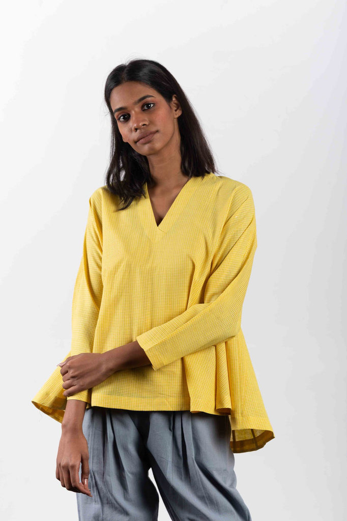 Yellow short top made from handwoven cotton in India.