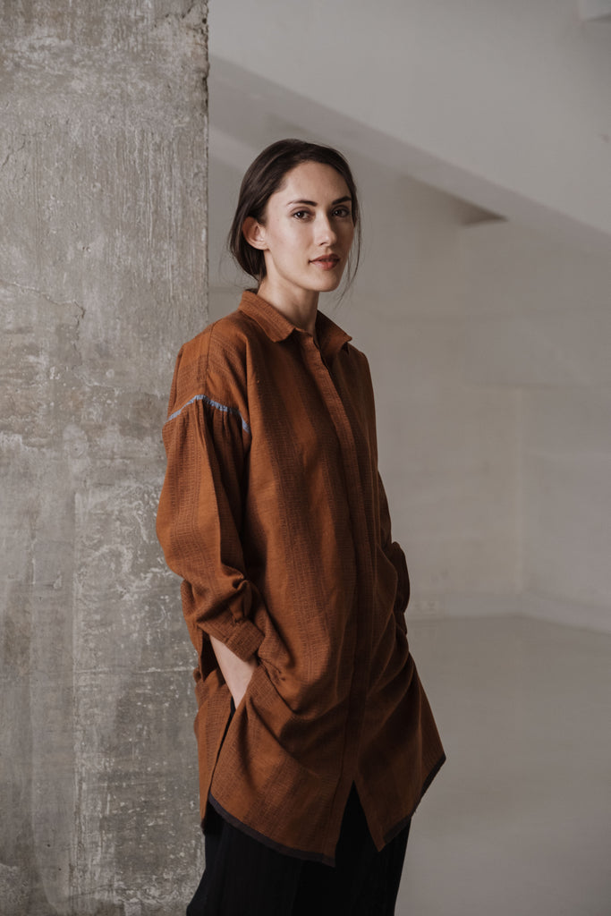 Shop minimalistic clothing. Indo-western pure cotton clothes. Brown handwoven long shirt with collar neck, full cuffed sleeves, and knee-length. Oversized silhouette shirts. Clothes for plus-size women. Available for bulk buy.