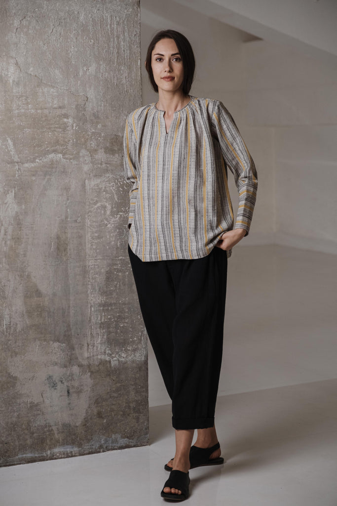 Fair trade clothing brands in India. Buy slow fashion clothing online. Textured yellow and grey striped top made from handwoven cotton material. The top has full sleeves with long fitted cuffs, a round V-shaped neck, and delicate gathers around the neck.