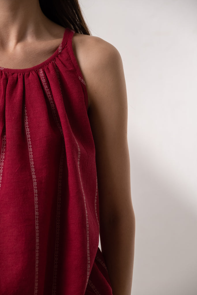 Environmentally conscious fashion. Clothing available for bulk business in USA, UK, India, France, Italy, Spain, Dubai. Pure cotton fabrics made by the weavers of Kachchh. Sleeveless red tank top with gathers around the neck.