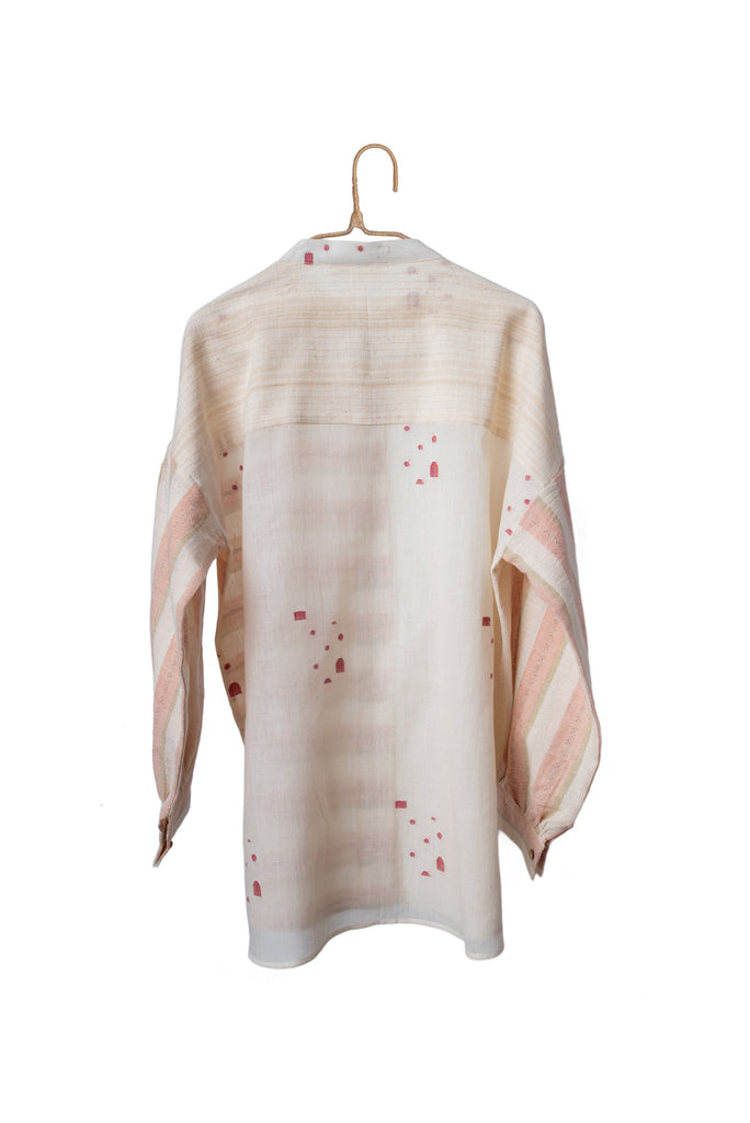 Striped organic cotton patchwork shirt made from handcrafted organic cotton fabric. It's a White and pink colored shirt with a closed neck, button down placket and long loose sleeves with cuffs.