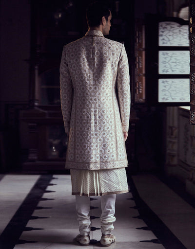 Ivory color short sherwani in raw silk fabric with all over intricate floral zal. Paired with  long lenth  kurta and churidar.