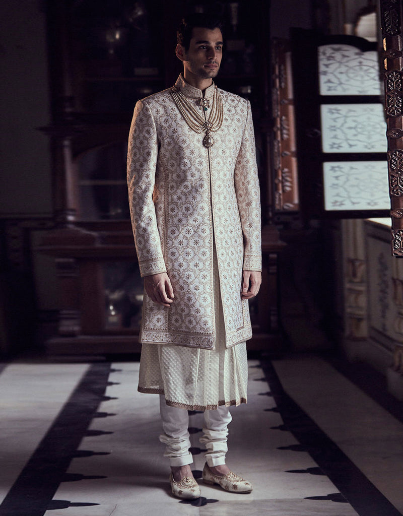 Ivory color short sherwani in raw silk fabric with all over intricate floral zaal, Paired with  long lenth  kurta and churidar.