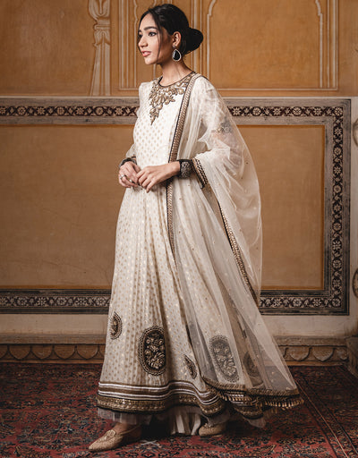 Asymmetric Long Kurta In Chanderi Brocade Featuring Zardozi Embroidery On The Neckline. Paired With A Tulle Dupatta And Churidar.