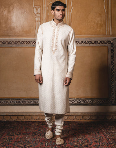 Ivory color kurta in chanderi zari brocade fabric ,with dori and hand embroidery on neck,collor and sleeves.paired with matching churidar.