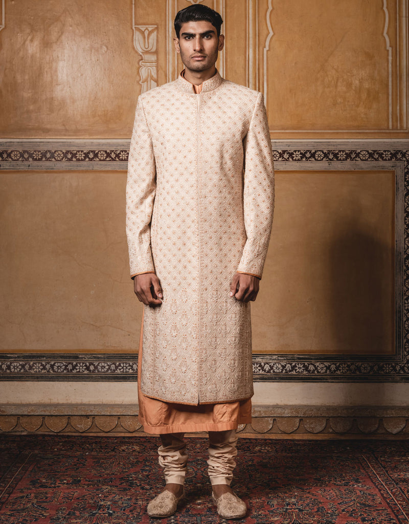 Gold color sherwani in matka silk fabric,with all over dori and zardosi embroidery.Paired with matching kurta and churidar.
