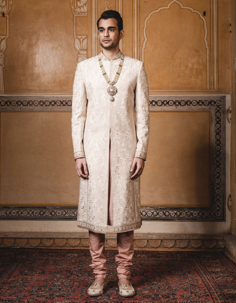Ivory color sherwani in matka silk fabric ,with all over intricate resham ,dori and badla work.Paired with ,long kurta and churidar.