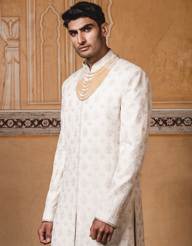 Ivory color sherwani ,handcrafted in pure georgette fabric with all over intricate lucknowi chikan and aari work.Paired with silk kurta and churidar .